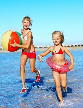 Children holding hands running on  beach. Stock Photo - 20654302