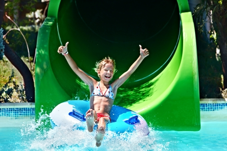 amusement park ride: Child on water slide at aquapark. Summer holiday.