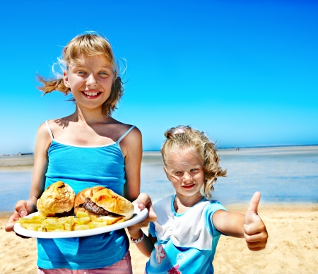 Child eating fast food at beach outdoor. photo