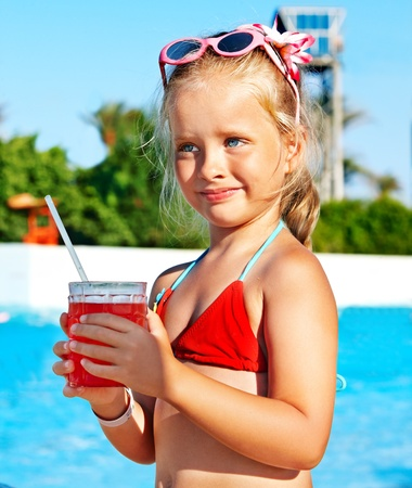 Child drinking soft drink near swimming pool. photo