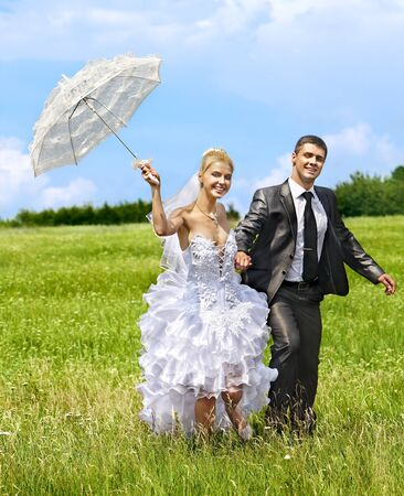 Happy bride and groom wedding running outdoor. photo