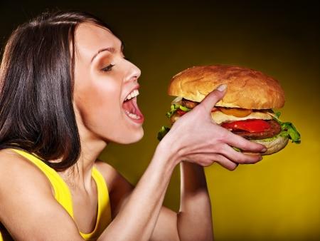 ätande: Slank kvinna äter hamburgare. Stockfoto