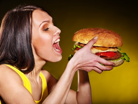 Slim woman eating hamburger. Stock Photo - 20654492