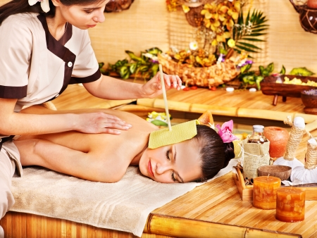 Woman getting massage with ear candle in bamboo spa. photo