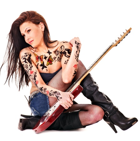 Young woman with tattoo playing guitar. Stock Photo