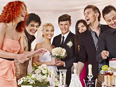 svatba: Skupina lidí u svatebního stolu s dortem.