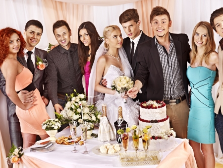 Group people at wedding table with cake.