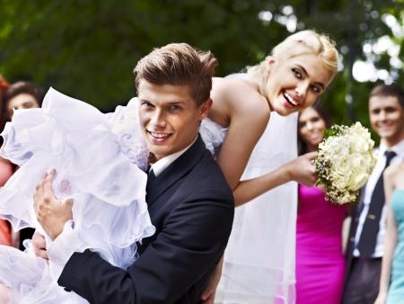 wedding celebration: Groom carries his bride over shoulder. Outdoor.