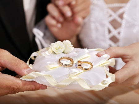 Hand holding pillow with wedding ring. photo