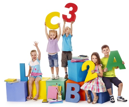 play school: Children sitting at cube hand up.