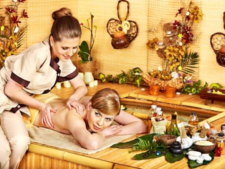 Woman getting stone massage in  spa near water. photo