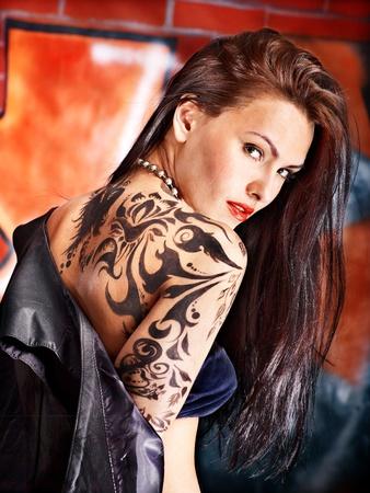 body paint: Mujer con el arte del cuerpo pared de ladrillo aganist graffiti.