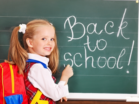 Happy child with backpack writting on blackboard. photo