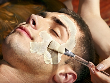 parlour: Man with clay facial mask in beauty spa.