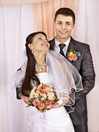 bridal couple: Happy wedding couple holding flower bouquet.