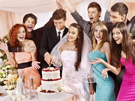 party food: Group people at wedding table cut cake.