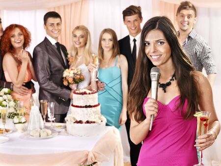 holiday food: Happy group people at wedding singing song. Stock Photo