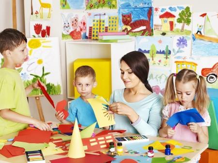 tanulás: Boldog gyermekek ollóval az osztályteremben.