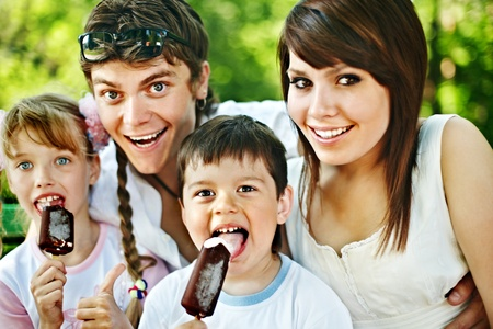 Happy family and group children eat ice cream. Outdoor. photo