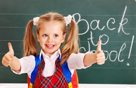 first day: Happy child near blackboard show thumb up.