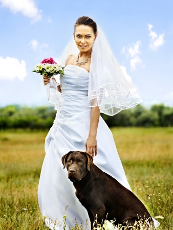Happy bride with dog. Wedding  outdoor. photo