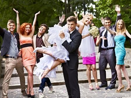 carries: Groom carries his bride over shoulder. Outdoor.