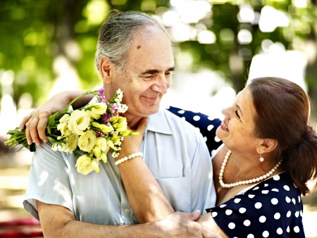 Happy old couple with flower outdoor. photo