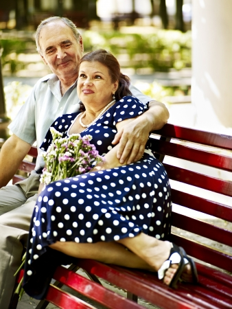 Old couple sit on bench. Outdoor. photo