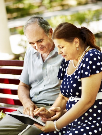 pix: Old couple with tablet pc sit on bench  . Outdoor.