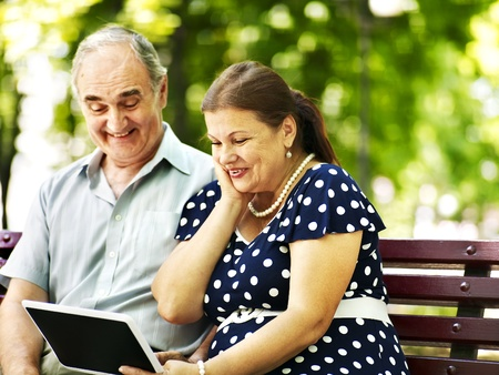 old pc: Old couple with tablet pc sit on bench  . Outdoor.