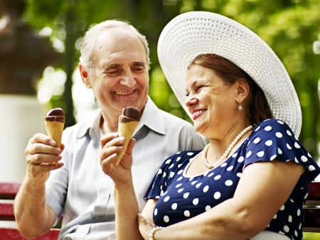 eating chocolate: Happy old couple eating ice-cream outdoor. Stock Photo
