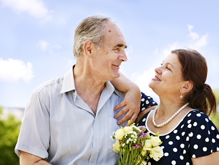 Portrait of  old couple with  bouquet at summer  outdoor. photo