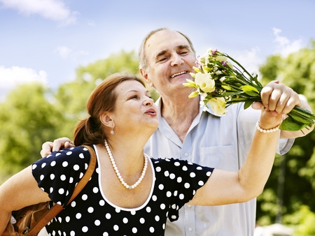 Happy old couple with  bouquet at summer  outdoor. photo