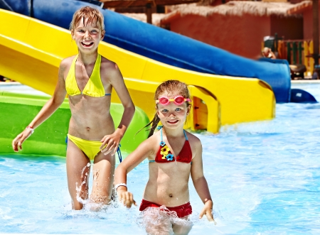 Children on water slide at aquapark. Summer holiday. photo