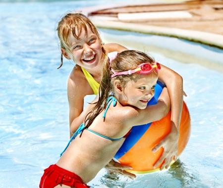 ball aqua: Little girl  playing beach ball swimming in pool. Stock Photo
