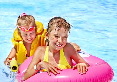 float tube: Children wearing life jacket in swimming pool.