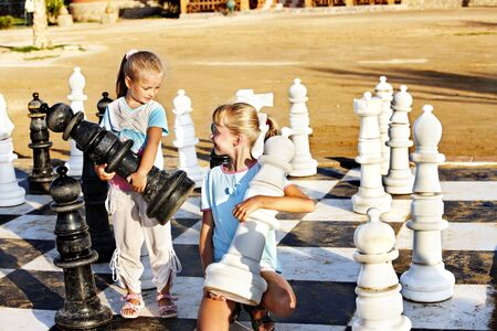 Children playing big chess outdoor. photo