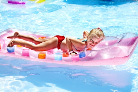 Child swimming on inflatable beach mattress. Stock Photo