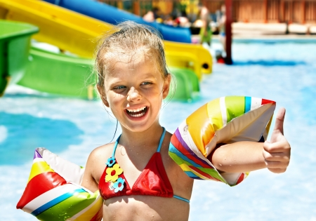 Child with armbands playing in swimming pool. Summer\ outdoor.