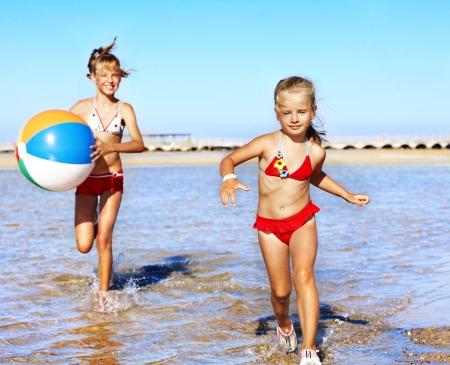 child in bikini: Children holding hands running on  beach.