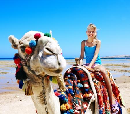 Toeristen kinderen rijden kameel op het strand van Egypte. Scherpte op een kameel.
