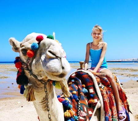 camel in desert: Tourists children riding camel  on the beach of  Egypt. Sharpness on a camel.