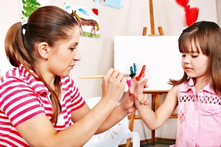 preschool education: Little girl painting  with teacher in preschool.