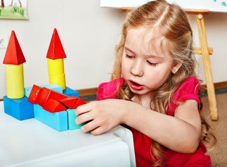 Child preschooler play wood block in play room. Child care. photo