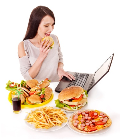 Woman eating fast food at work. Isolated. photo
