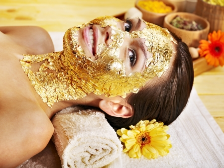 tratamientos corporales: Mujer recibiendo m?scara de oro facial. Foto de archivo