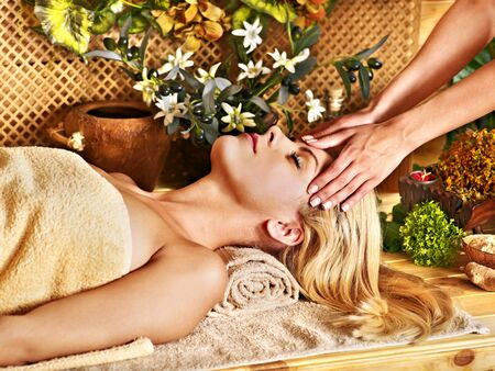 head massage: Blond woman getting facial massage in tropical beauty spa.