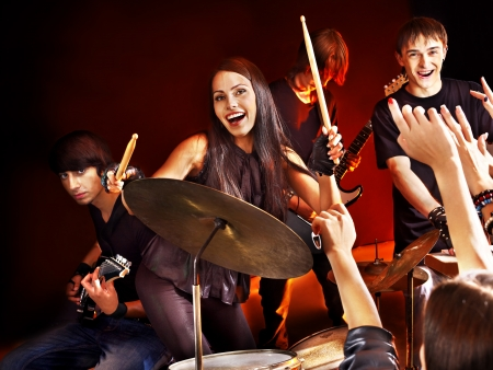 Woman beat guitar: Musical group playing in night club.