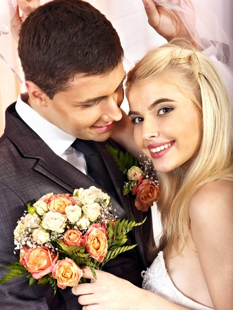 young couple smiling: Happy wedding couple holding flower bouquet.