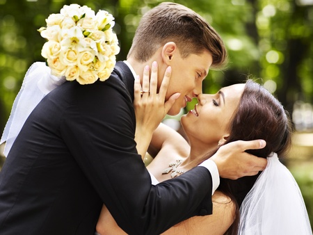 Bride and groom with flower kissing  outdoor. photo